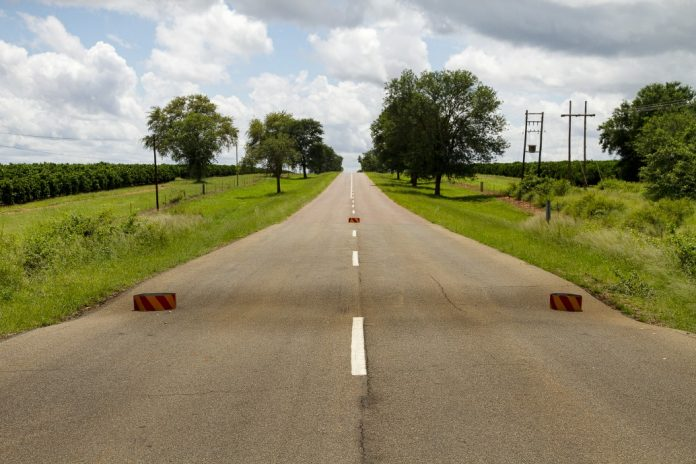 Scene showing a country road with a massive sinkhole forming in the middle
