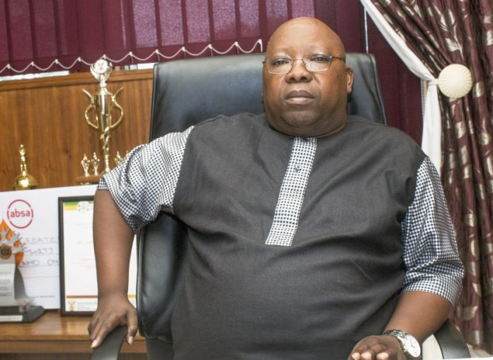 Matlala sitting in his office chair behind his desk
